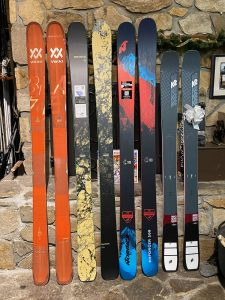 four sets of skis against a stone fireplace